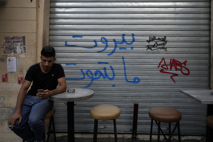 A man checks his mobile phone as he sits outside a bar in the Mar Mikhael neighborhood in Beirut, Lebanon, Saturday, July 17, 2021. A year after a deadly blast at the Beirut port killed more than 200 people, families of the victims are consumed with winning justice for their loved ones and punishing Lebanon's political elite, blamed for causing the disaster through their corruption and neglect. (AP Photo/Hassan Ammar)