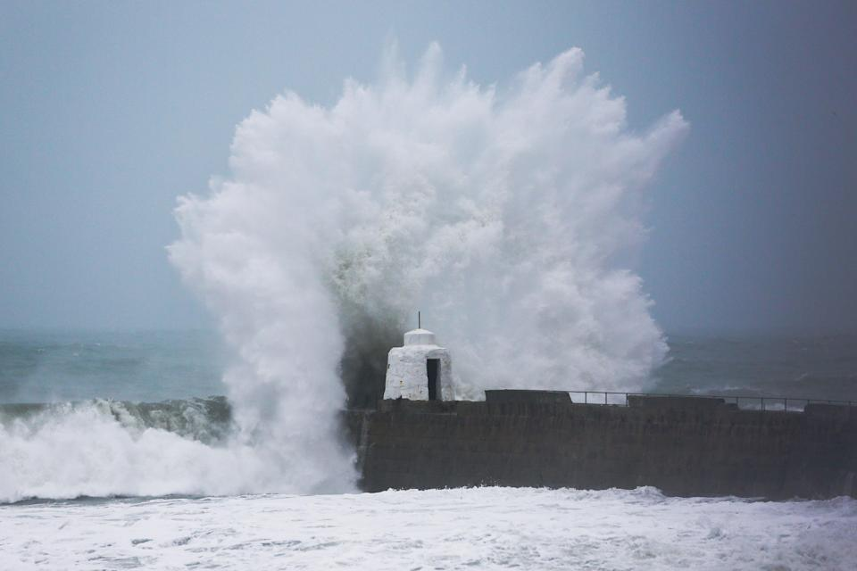 Waves pound against the harbour wall at Portreath in Cornwall in 2020 (PA) (PA Archive)
