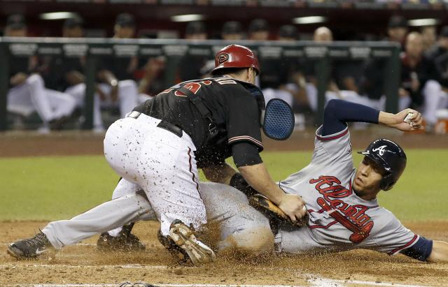 Atlanta Braves' Andrelton Simmons, right, scores ahead of the tag by Arizona Diamondbacks' Miguel Montero during the third inning of a baseball game Saturday, June 7, 2014, in Phoenix. (AP Photo/Ross D. Franklin)