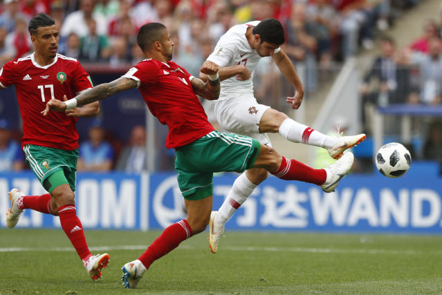 Portugal's Goncalo Guedes, right, shots on target as Morocco's Manuel Da Costa, center, challenges for the ball during the group B match between Portugal and Morocco at the 2018 soccer World Cup in the Luzhniki Stadium in Moscow, Russia, Wednesday, June 20, 2018. (AP Photo/Matthias Schrader)
