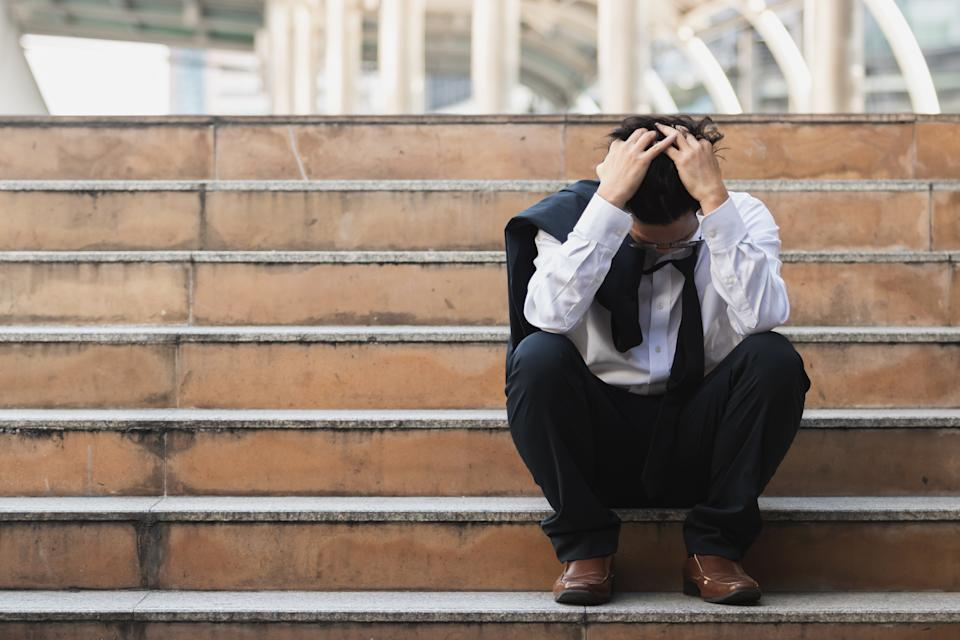 Upset stressed young business man in suit with hands on head sitting on stairs. Unemployment and layoff concept.