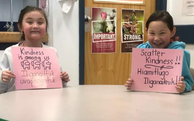 Two students from Helen Kalvak Elihakvik School in Ulukhaktok, N.W.T. show the signs they made to celebrate Pink Shirt Day. Each sign the students made were in English and Inuinnaqtun and included phrases of kindness.