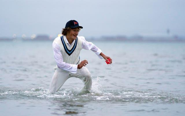 A fielder wades in to help his colleagues (Andrew Matthews/PA)