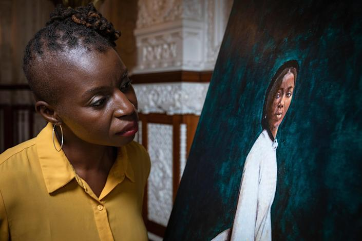 Artist Hannah Uzor and her painting of Bonetta. / Credit: Christopher Ison/English Heritage