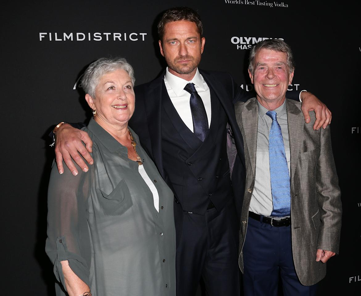 """HOLLYWOOD, CA - MARCH 18: Actor Gerard Butler (C) and his mother and father attend the Premiere of FilmDistrict's """"Olympus Has Fallen"""" at the ArcLight Cinemas Cinerama Dome on March 18, 2013 in Hollywood, California.  (Photo by Frederick M. Brown/Getty Images)"""