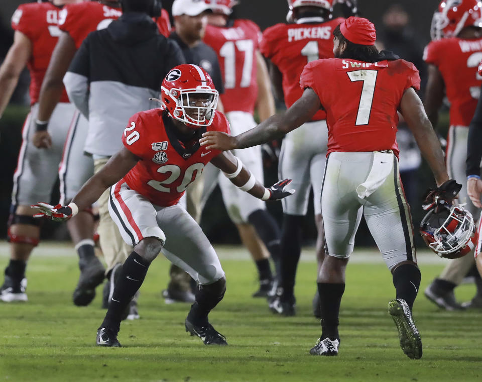 Georgia defensive back J.R. Reed, left, celebrates after stopping Missouri on fourth down with tailback D'Andre Swift (7) to take over on downs in the final minutes of the fourth quarter and preserve a shutout in an NCAA college football game Saturday, Nov. 9, 2019, in Athens, Ga. (Curtis Compton/Atlanta Journal Constitution via AP)