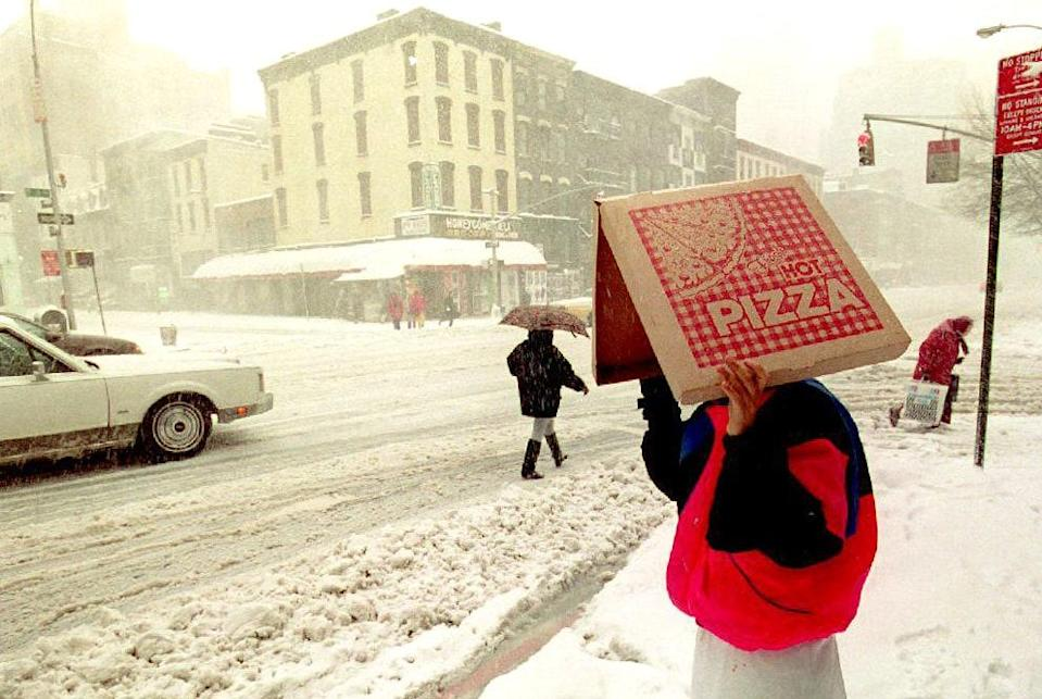 A pizza delivery man shields himself from the epic blizzard that hit New York City in March 1993—one of the worst storms in a decade.