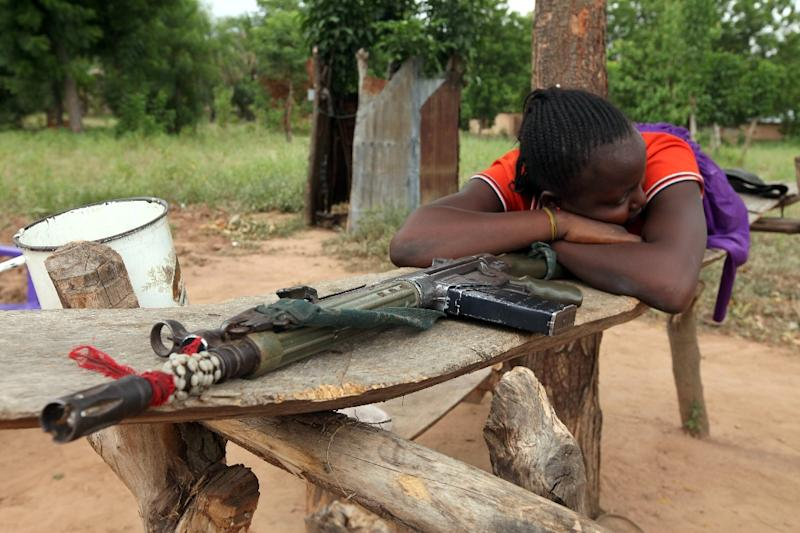 A woman lies on a riffle which she claims belong to her husband for self-defence (AFP Photo/Emmanuel Arewa)