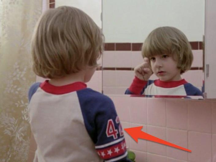 """the son in """"The Shining"""" is wearing a t shirt with the number 42 on the sleeve and staring in the bathroom mirror"""