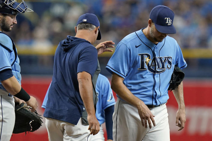 Tampa Bay Rays manager Kevin Cash, center, takes starting pitcher Rich Hill, right, out of the game against the Baltimore Orioles during the fourth inning of a baseball game Saturday, June 12, 2021, in St. Petersburg, Fla. Looking on is catcher Mike Zunino. (AP Photo/Chris O'Meara)