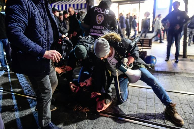Turkish anti-riot police officers detain a protester during a demonstration against the US and Israel on December 9, 2017 in the Kadikoy district of Istanbul