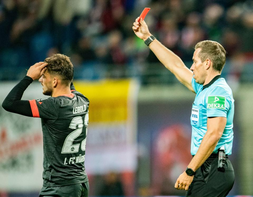 A referee brandishes a red card, this time not at himself.