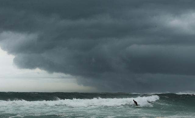 SYDNEY, AUSTRALIA - JANUARY 29: A surfer takes on the large swells as storm clouds gather at Coogee Beach after winds and rain battered Sydney last night on January 29, 2013 in Sydney, Australia. Parts of Sydney are experienced record rainfall after ex-cyclone Oswald swept through the city last night. (Photo by Mark Metcalfe/Getty Images)