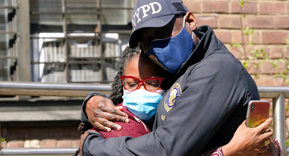 An NYPD police officer hugs a woman after the triple murder-suicide.