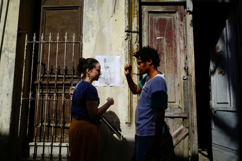 "FILE PHOTO: Organizer of the ""00Biennial"" Luis Manuel Otero Alcantara speaks to Brazilian artist Polyanna Morgana as she hangs a poster on a wall in Havana"