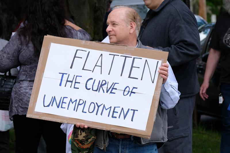 MILFORD, PENNSYLVANIA, UNITED STATES - 2020/05/15: A man holds a placard saying, Flatten the Curve of Unemployment, during the demonstration. Pike County Pennsylvania and Milford, Pennsylvania area residents protest against Governor Wolf and the ongoing business closures. (Photo by Preston Ehrler/SOPA Images/LightRocket via Getty Images)