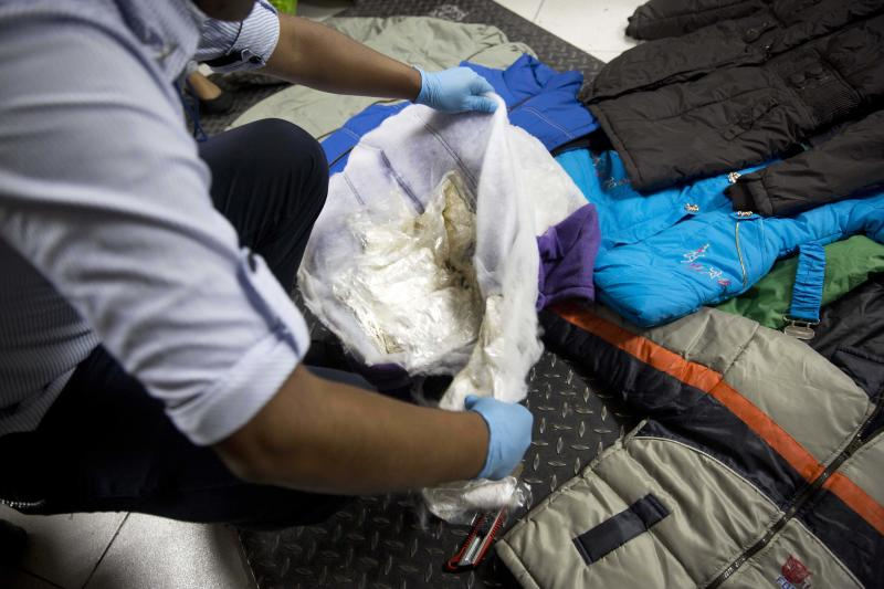 In this Jan. 26, 2014 photo, a police officer discovers bags of cocaine in the luggage of Liz Rabines, from Spain, at the anti-narcotics police station before she tried to embark a plane for Spain at the Jorge Chavez International Airport in Lima, Peru. While most of the mules are men, a growing number are women. (AP Photo/Martin Mejia)