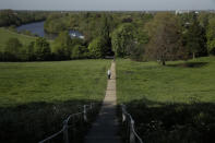 A person walks on a path towards the River Thames in Richmond, London, during the lockdown for the coronavirus, Tuesday, April 21, 2020. The highly contagious COVID-19 coronavirus has impacted on nations around the globe, many imposing self isolation and exercising social distancing when people move from their homes. (AP Photo/Matt Dunham)