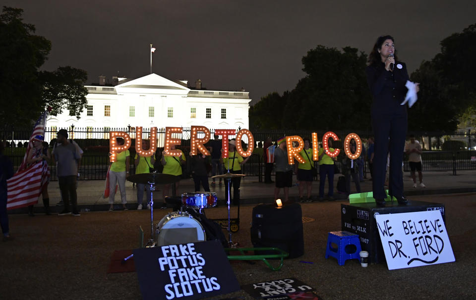 FILE - In this Sept. 20, 2018 file photo, Jennice Fuentes, right, of Power 4 Puerto Rico, speaks outside the White House in Washington, during a vigil commemorating the one-year anniversary of Hurricane Maria hitting Puerto Rico. Puerto Rico is getting much of the money it needs to rebuild its power grid three years after it was wiped out by Hurricane Maria, the island territory's governor and the White House said Friday.(AP Photo/Susan Walsh)