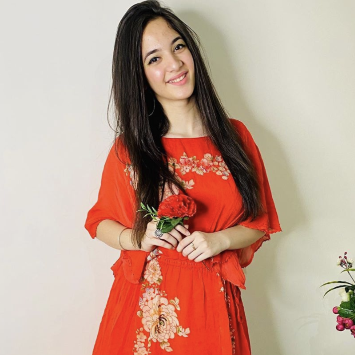 Siya is seen holding a red flower while smiling.