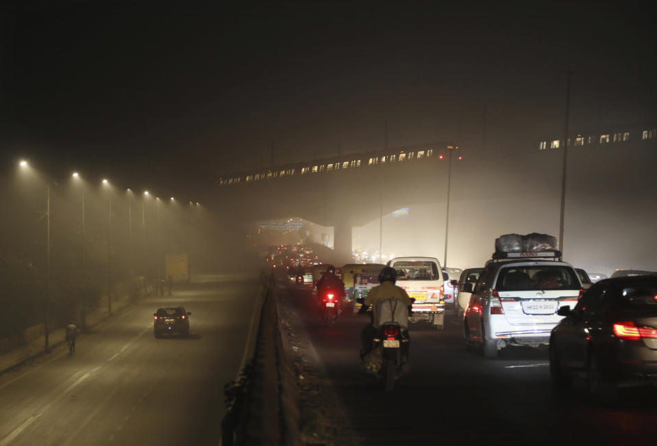 Commuters drive on a road engulfed in smog in New Delhi, India, Thursday, Nov. 5, 2020. A thick quilt of smog lingered over the Indian capital and its suburbs on Friday, fed by smoke from raging agricultural fires that health experts worry could worsen the city's fight against the coronavirus. Air pollution in parts of New Delhi have climbed to levels around nine times what the World Health Organization considers safe, turning grey winter skies into a putrid yellow and shrouding national monuments. (AP Photo/Manish Swarup)