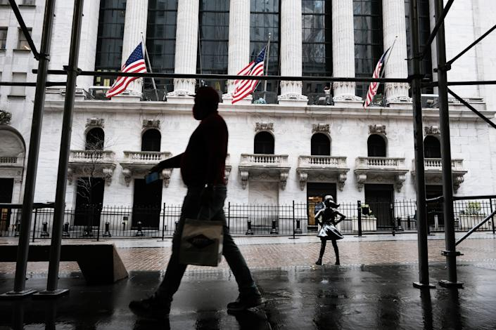 NEW YORK, NEW YORK - APRIL 15: People walk by the New York Stock Exchange on April 15, 2021 in New York City. After major companies reported strong earnings and new economic data points to a rebound in consumer spending, U.S. stocks climbed to record levels on Thursday. (Photo by Spencer Platt/Getty Images)