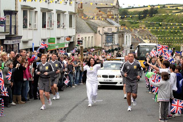 This photograph issued by LOCOG shows torchbearer Nicole Martin carrying the Olympic torch during the leg of the torch relay between the villages of Rosudgeon and Helston in south west England Saturday May 19, 2012. The torch will be carried all over the British Isles by 8,000 chosen volunteers, mostly local heroes. Its 8,000-mile (12,875-kilometer) journey will linger on the iconic sites _ Big Ben, Stonehenge, the white cliffs of Dover _ and speed past less appealing areas. It ends up July 27 at the Olympic Stadium in London. (AP Photo/ Yui Mok/LOCOG, HO)