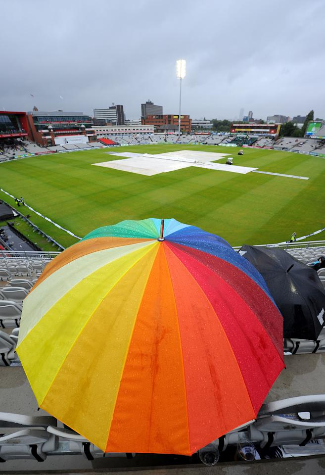 Fans shelter under umbrellas as rain stops play during day five of the Third Investec Ashes test match at Old Trafford Cricket Ground, Manchester.