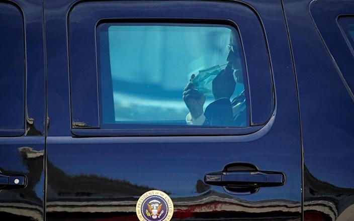 Biden removes his mask inside his walled car