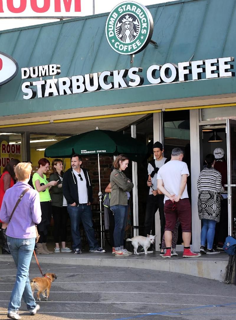 "People line up at Dumb Starbucks coffee in Los Angeles Monday, Feb. 10, 2014. The store resembles a Starbucks with a green awning and mermaid logo, but with the word ""Dumb"" attached above the Starbucks sign. Spokeswoman Laurel Harper says the store is not affiliated with Starbucks and, despite the humor, the store cannot use the Starbucks name. (AP Photo/Damian Dovarganes)"