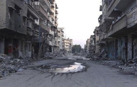 A general view shows a deserted street filled with debris of damaged buildings in Deir al-Zor