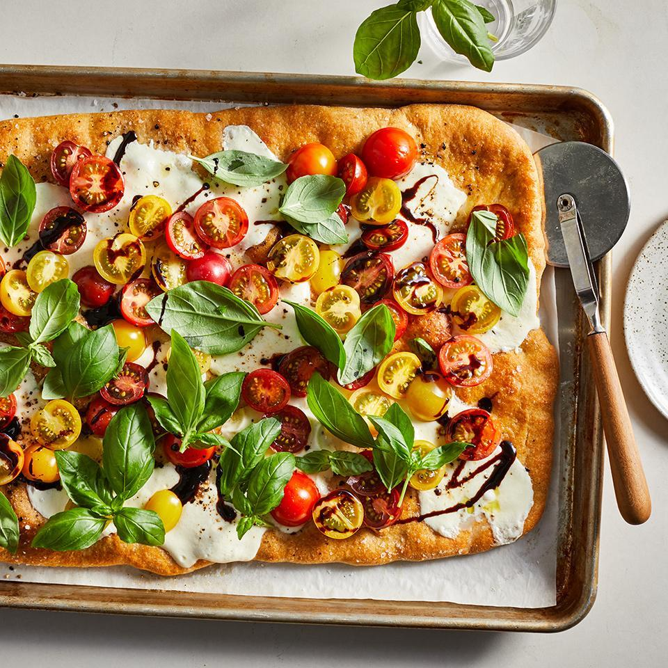 """<p>This light and flavorful caprese pizza is ready when the tomatoes are just heated through and the mozzarella cheese is slightly melted. If you want a little more on this pizza, it'd be delicious with a few slices of prosciutto. Chef tip: let your dough come up to room temperature before you stretch it--it'll make it much easier to work with. <a href=""""http://www.eatingwell.com/recipe/275492/sheet-pan-caprese-pizza/"""" rel=""""nofollow noopener"""" target=""""_blank"""" data-ylk=""""slk:View recipe"""" class=""""link rapid-noclick-resp""""> View recipe </a></p>"""