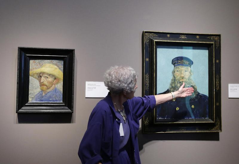 FILE - In a June 13, 2013 file photo, Detroit Institute of Arts docent Lea Schelke points out details in the Portrait of Postman Roulin by Van Gogh displayed at the museum in Detroit. A closer look at the DIA art collection now being appraised by Christie's. It's report to state-appointed emergency manager Kevyn Orr could come out by mid-December. It's looking more and more like that's what debtors want to go after. (AP Photo/Carlos Osorio, File)