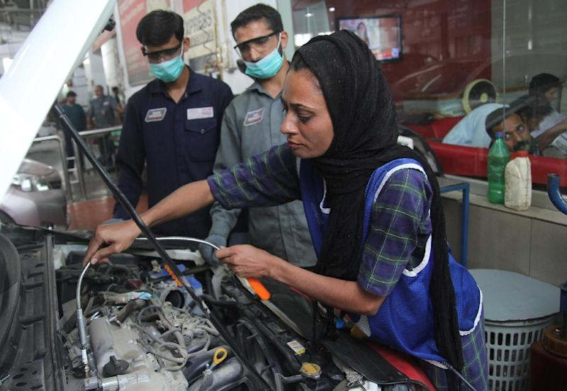 Pakistani motor mechanic Uzma Nawaz, 24, fixes a car at a workshop in Multan (AFP Photo/S.S. Mirza)