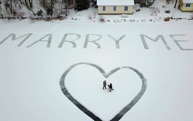 Gavin Becker had his family's help etching out the big question with a snow blower in 25-foot-tall letters - Ed Becker
