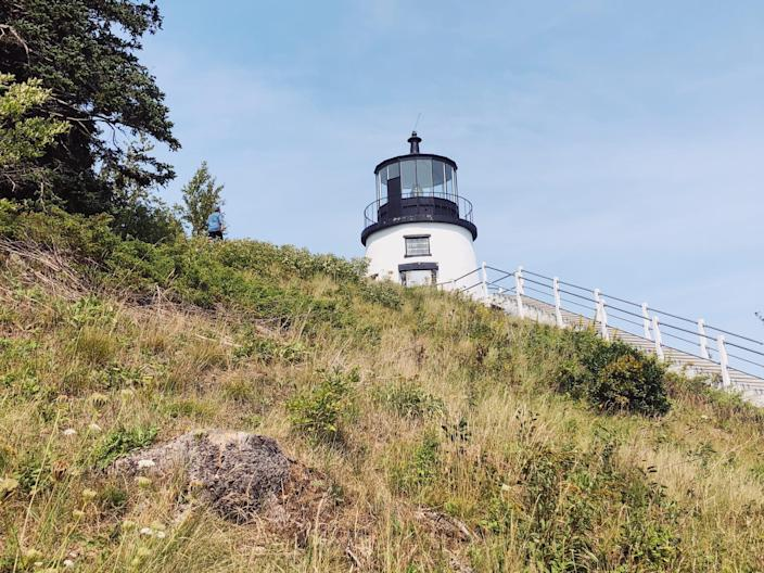 A black and white lighthouse peaking over the edge of a grassy hill