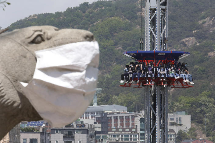 People wearing face masks as a precaution against the coronavirus ride Gyro Drop as they visit to celebrate Children's Day at Children's Grand Park in Seoul, South Korea, Wednesday, May 5, 2021. (AP Photo/Ahn Young-joon)