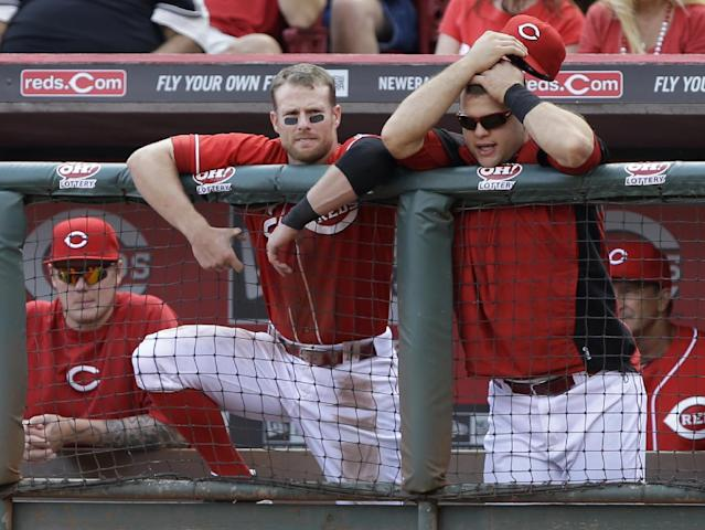 Cincinnati Reds' Zack Cozart, left, and Devin Mesoraco watch from the dugout in the ninth inning of a baseball game against the Pittsburgh Pirates, Saturday, Sept. 28, 2013, in Cincinnati. Pittsburgh won 8-3. (AP Photo/Al Behrman)