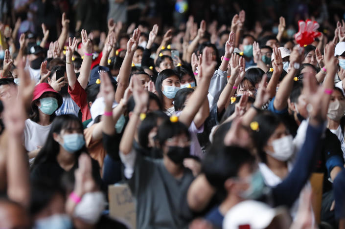 """A crowd flashes the three-finger protest gesture during a student rally in Bangkok Saturday, Nov. 21, 2020. Organized by a group that mockingly calls themselves """"Bad Students,"""" the rally calls for educational reforms and also supports the broader pro-democracy movement's demands for constitutional change. (AP Photo/Sakchai Lalit)"""