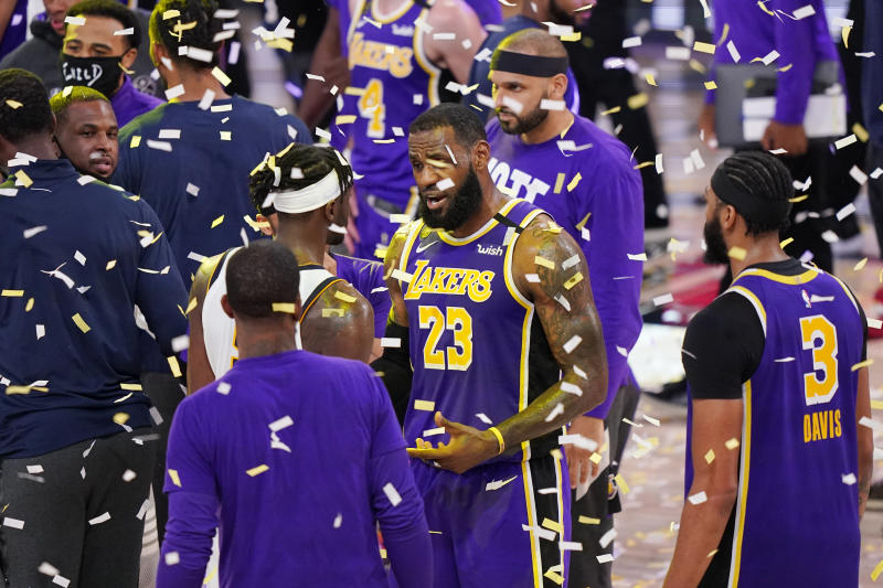 Los Angeles Lakers' LeBron James (23) talks with players as confetti falls after the Lakers beat the Denver Nuggets in an NBA conference final playoff basketball game Saturday, Sept. 26, 2020, in Lake Buena Vista, Fla. The Lakers won 117-107 to win the series 4-1. (AP Photo/Mark J. Terrill)