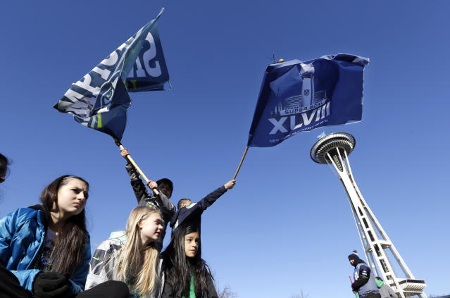 Seattle Seahawks fans cheer as they wait for the Super Bowl champions parade to begin Wednesday, Feb. 5, 2014, in Seattle. The Seahawks beat the Denver Broncos 43-8 in NFL football's Super Bowl XLVIII on Sunday.(AP Photo/Elaine Thompson)