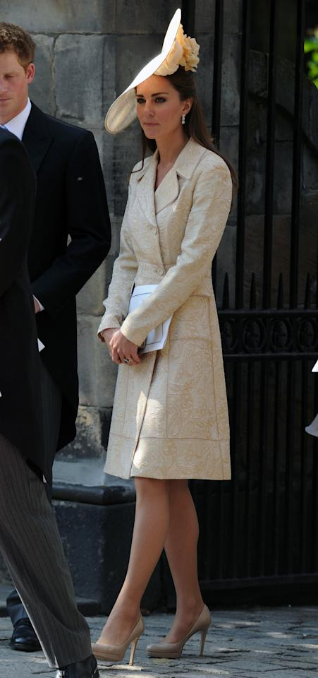 <p>For Zara Phillips' wedding to Mike Tindall, Kate donned a gold brocade coat by Day Birger et Mikkelsen and a large hat designer by Gina Foster. Her shoes and bag were both from L.K. Bennett.</p><p><i>[Photo: PA]</i></p>