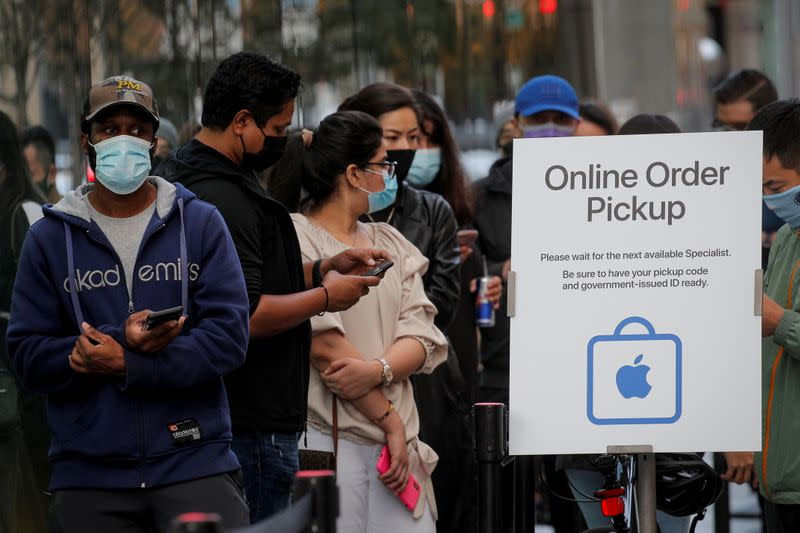 Customers wait in line outside an Apple Store to pick up Apple's new 5G iPhone 12 in Brooklyn, New York