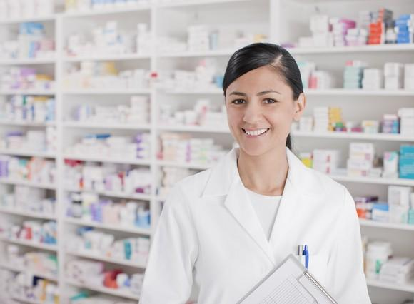 Woman in white lab coat holding clipboard in front of shelves of prescription drug bottles and containers.