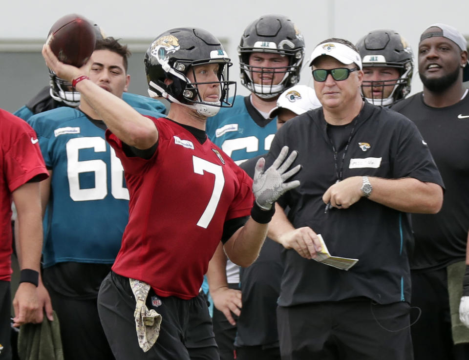 Jacksonville Jaguars quarterback Nick Foles (7) throws a pass as head coach Doug Marrone, front right, looks on during an NFL football practice at the teams training facility, Friday, July 26, 2019, in Jacksonville, Fla. (AP Photo/John Raoux)