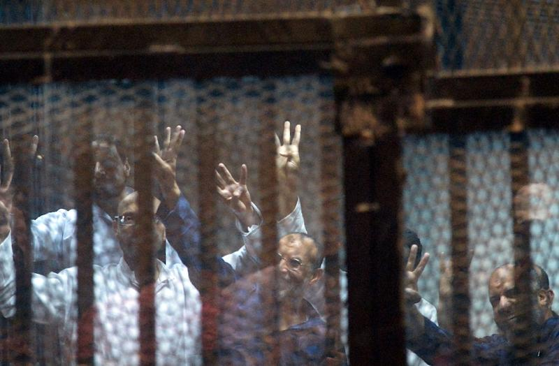 Top Egyptian Muslim Brotherhood leaders Essam el-Erian (C) and Mohamed Beltagy (R) stand with fellow accused in the defendents cage during their trial in Cairo, on April 21, 2015 (AFP Photo/Mohamed El-Shahed)