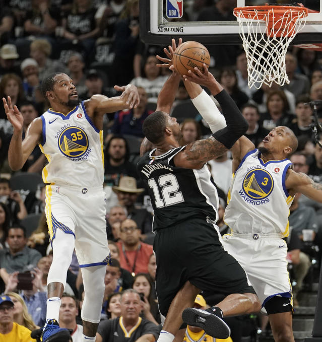 San Antonio Spurs' LaMarcus Aldridge (12) shoots against Golden State Warriors' David West (3) and Kevin Durant during the first half of Game 4 of a first-round NBA basketball playoff series in San Antonio, Sunday, April 22, 2018, in San Antonio. (AP Photo/Darren Abate)