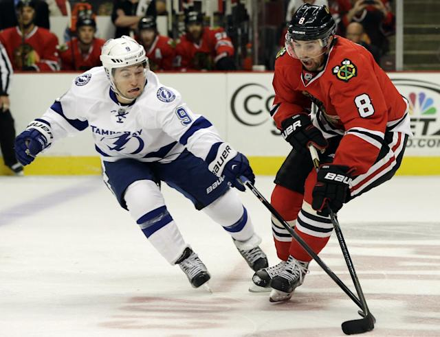 Tampa Bay Lightning's Tyler Johnson, left, and Chicago Blackhawks' Nick Leddy (8) vie for the puck during the first period of an NHL hockey game in Chicago, Saturday, Oct. 5, 2013. (AP Photo/Nam Y. Huh)