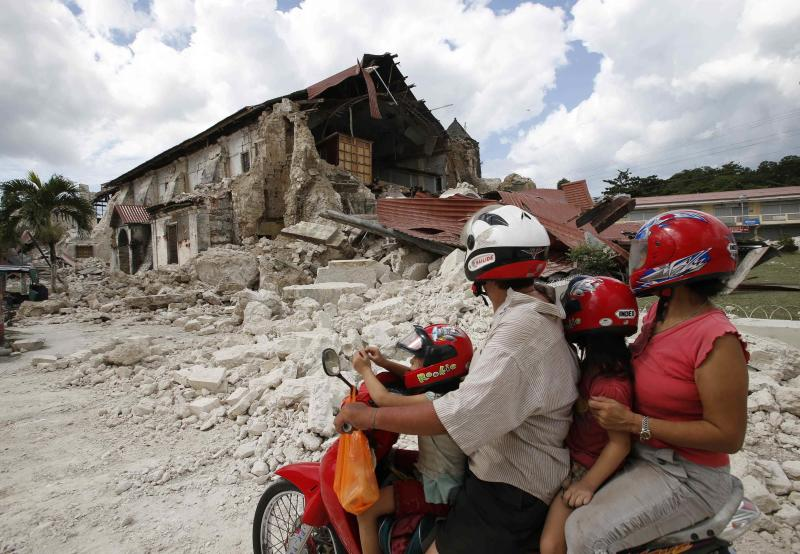 Family riding a motorcycle looks at a damaged church after an earthquake in the tourist town of Lobok