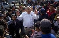 Luis Bustamante, an official from the Mexican state of Baja California, tries to answer questions from a group of Central American migrants, as they decide whether to relocate another shelter in Tijuana, Mexico, Friday, Nov. 30, 2018. Authorities in Tijuana said Friday they have begun moving Central American migrants from an overcrowded shelter on the border to an events hall further away. (AP Photo/Gregory Bull)